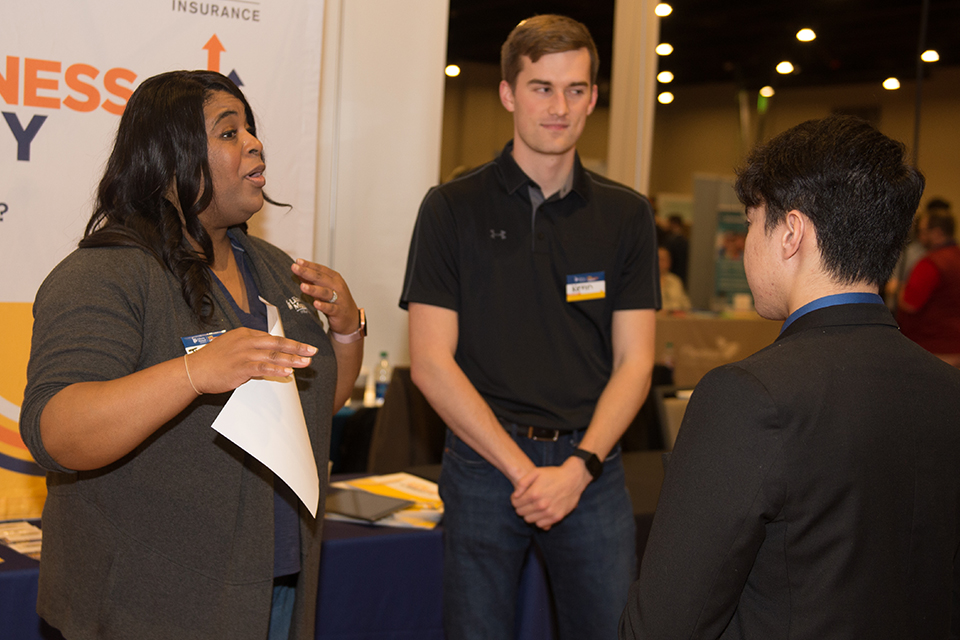 Recruiters from Liberty Mutual connect with a student at a job fair.