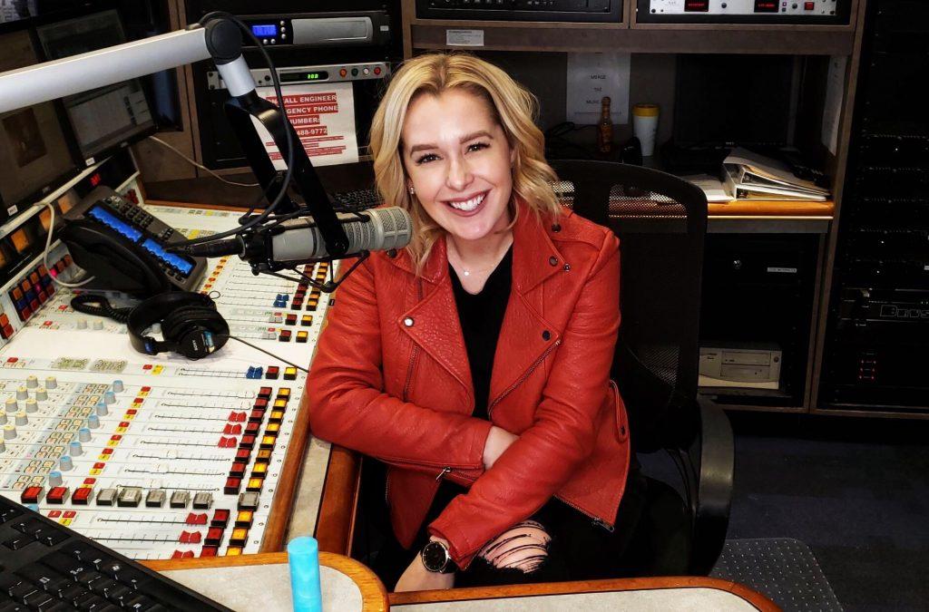 Alumna Katie Neal behind the microphone