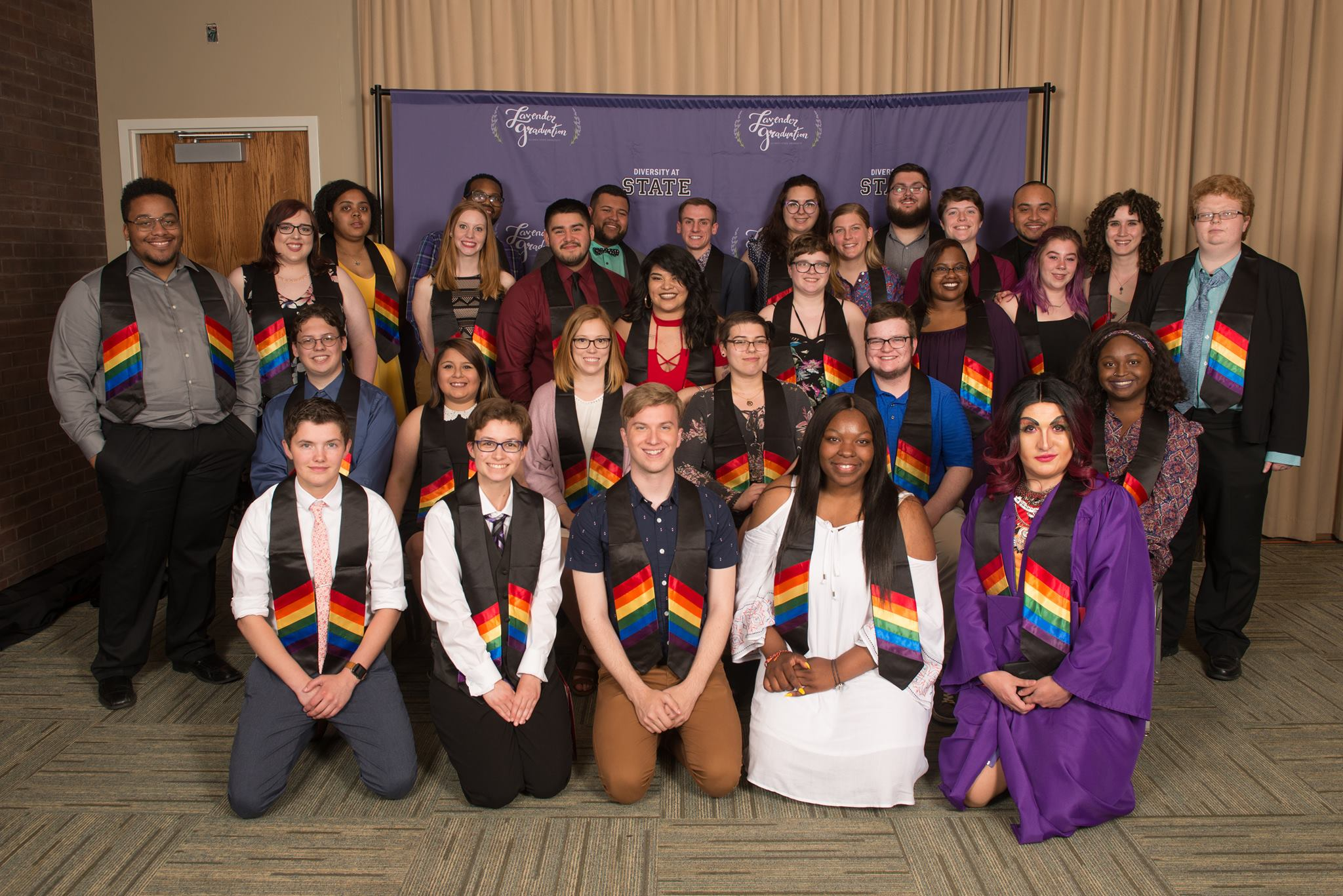 students smiling and wearing drapes with a rainbow design