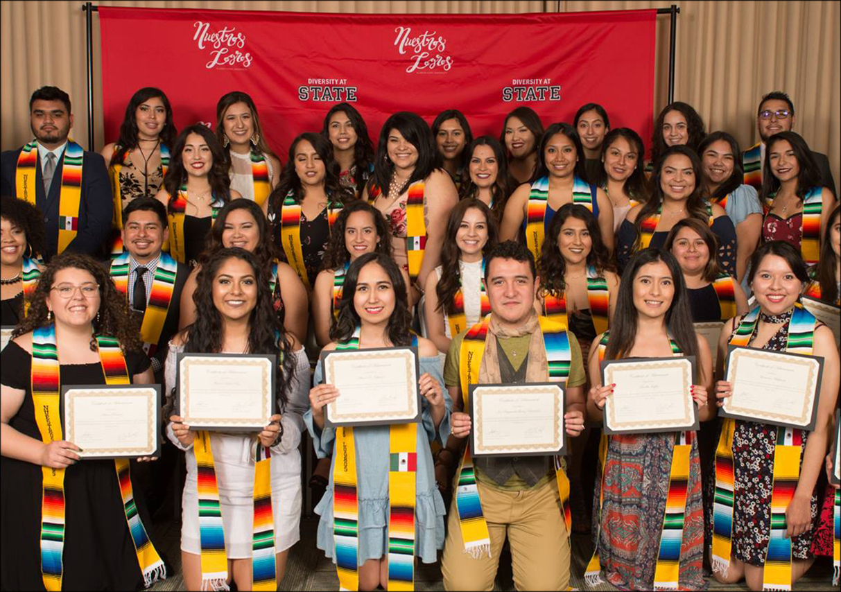 Students smiling and holding certificates and wearing graduation drapes