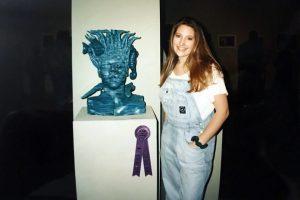 Women standing next to sculpted head bust.
