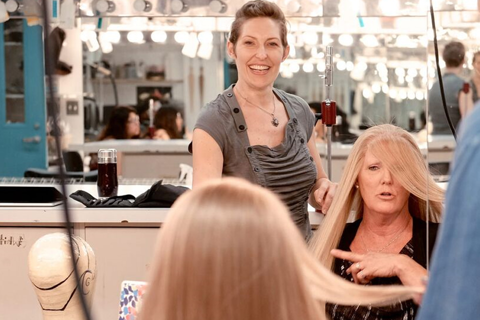 woman styling another woman's hair in front of mirror