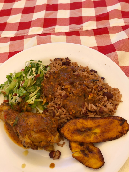 Lunch containing a salad, rice, chicken and plantains.