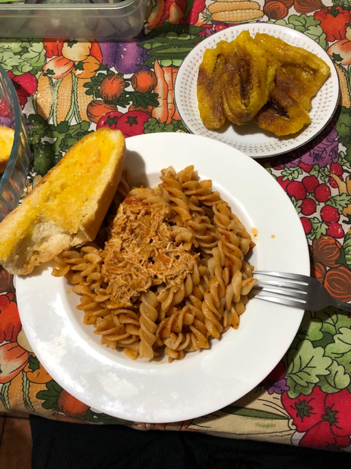 Dinner containing chicken, pasta, garlic bread and plantains topped with brown sugar.