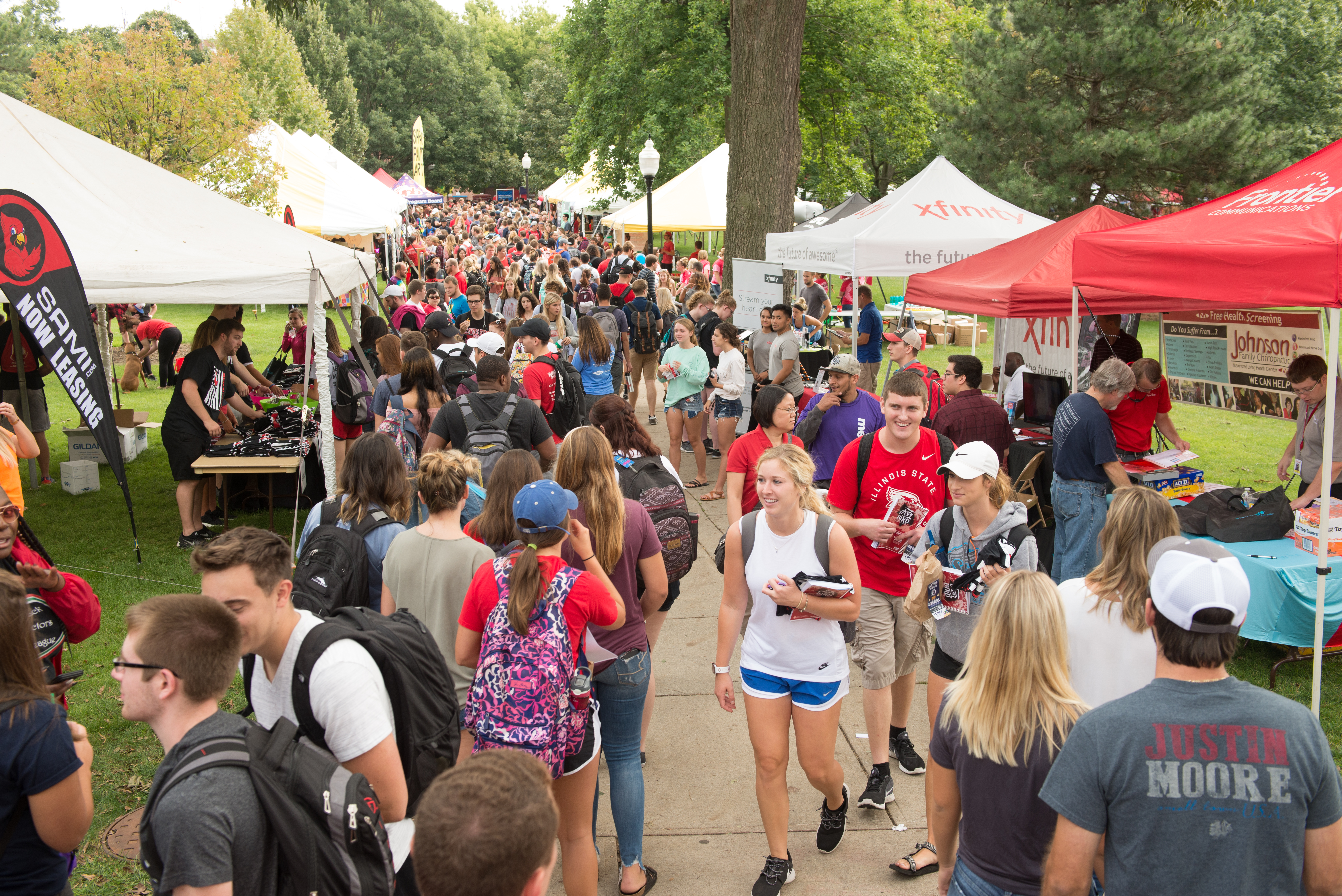 A large group of students on Illinois State's Quad between tents and tables set up for Festival ISU