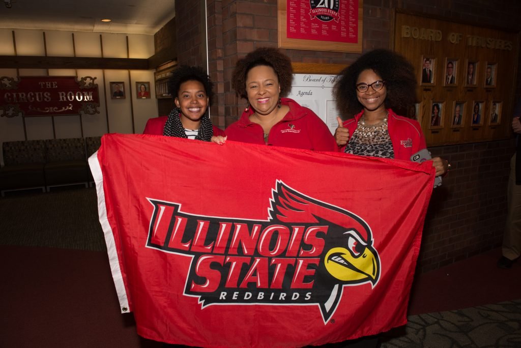 Three people holding a flag that has the words Illinois State Redbirds on it.