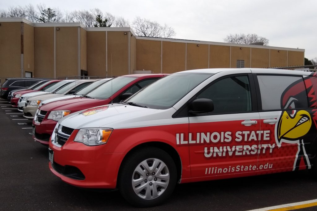 Row of University minivans parked in front of the John Green Building