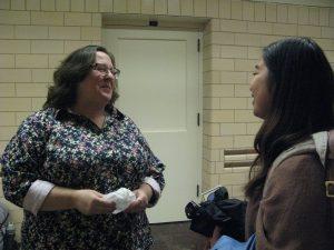 two women speaking in a hallway