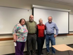 4 adults standing in a classroom