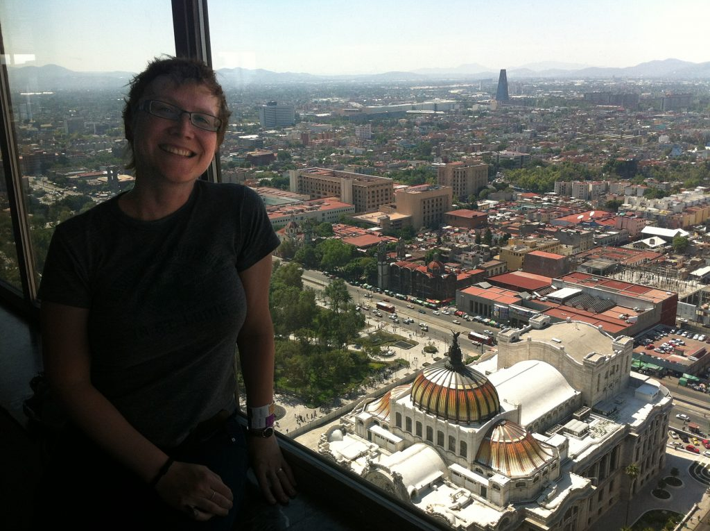 woman at a window with a view of Mexico City in the background