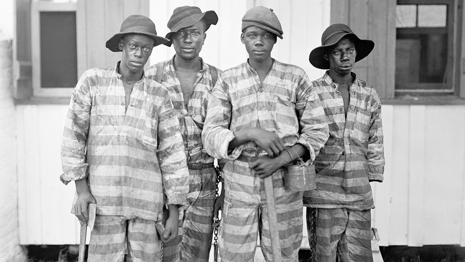 Four men standing in prison uniforms
