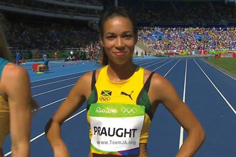 A woman smiling, standing on a running track