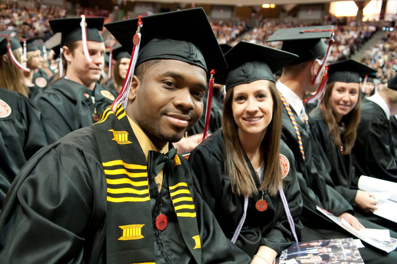 Students smile and pose in cap and gown at Illinois State graduation