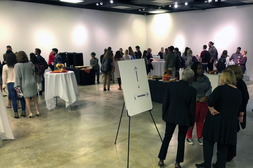 Image of students and alumni networking over refreshments.