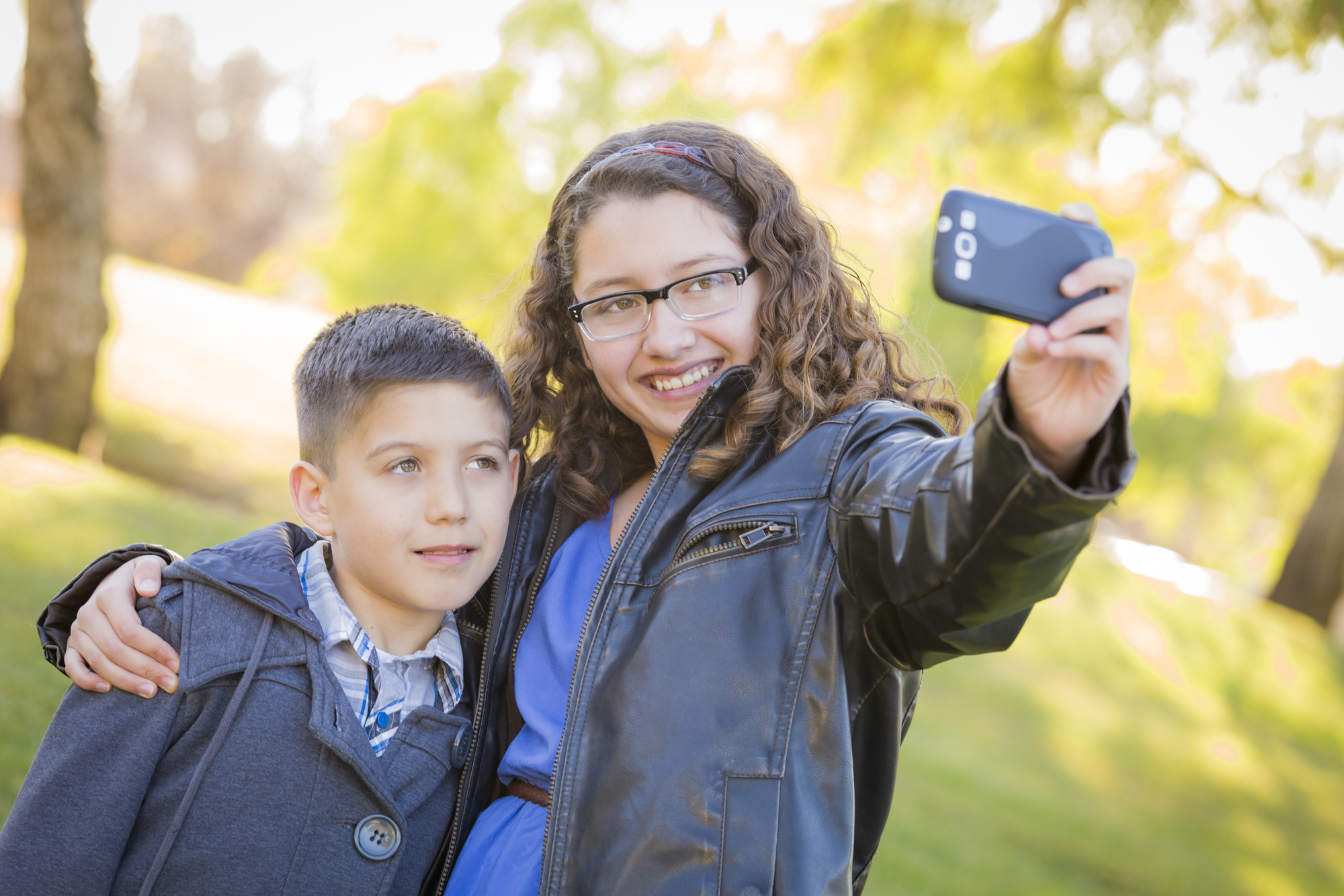 Brother and Sister Taking Cell Phone Picture of Themselves Outdoors At The Park.