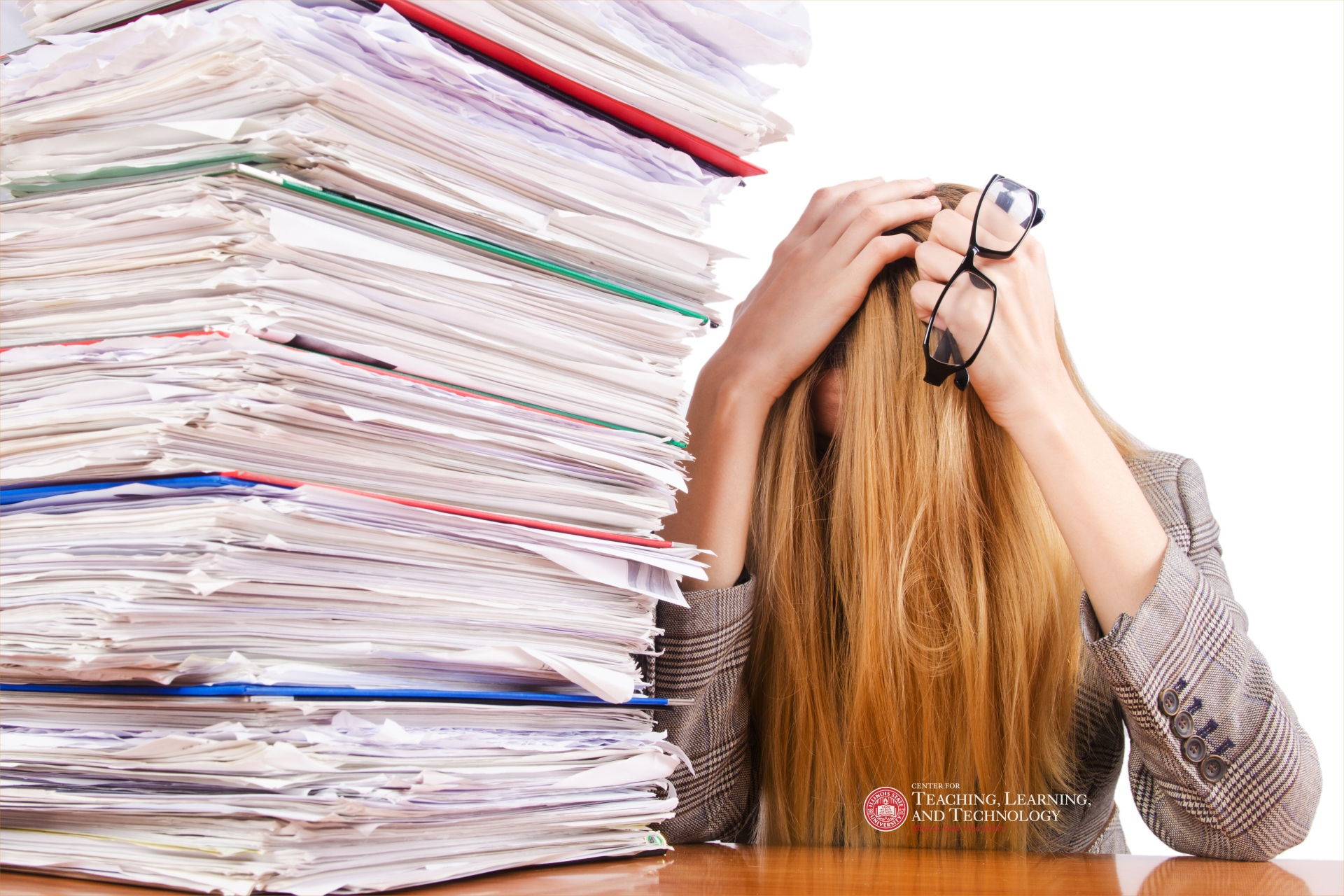Woman with head covered next to a pile of student portfolios.