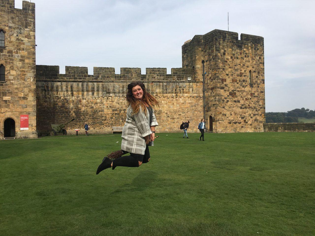 Hannah Lehman jumping in front of castle in Scotland