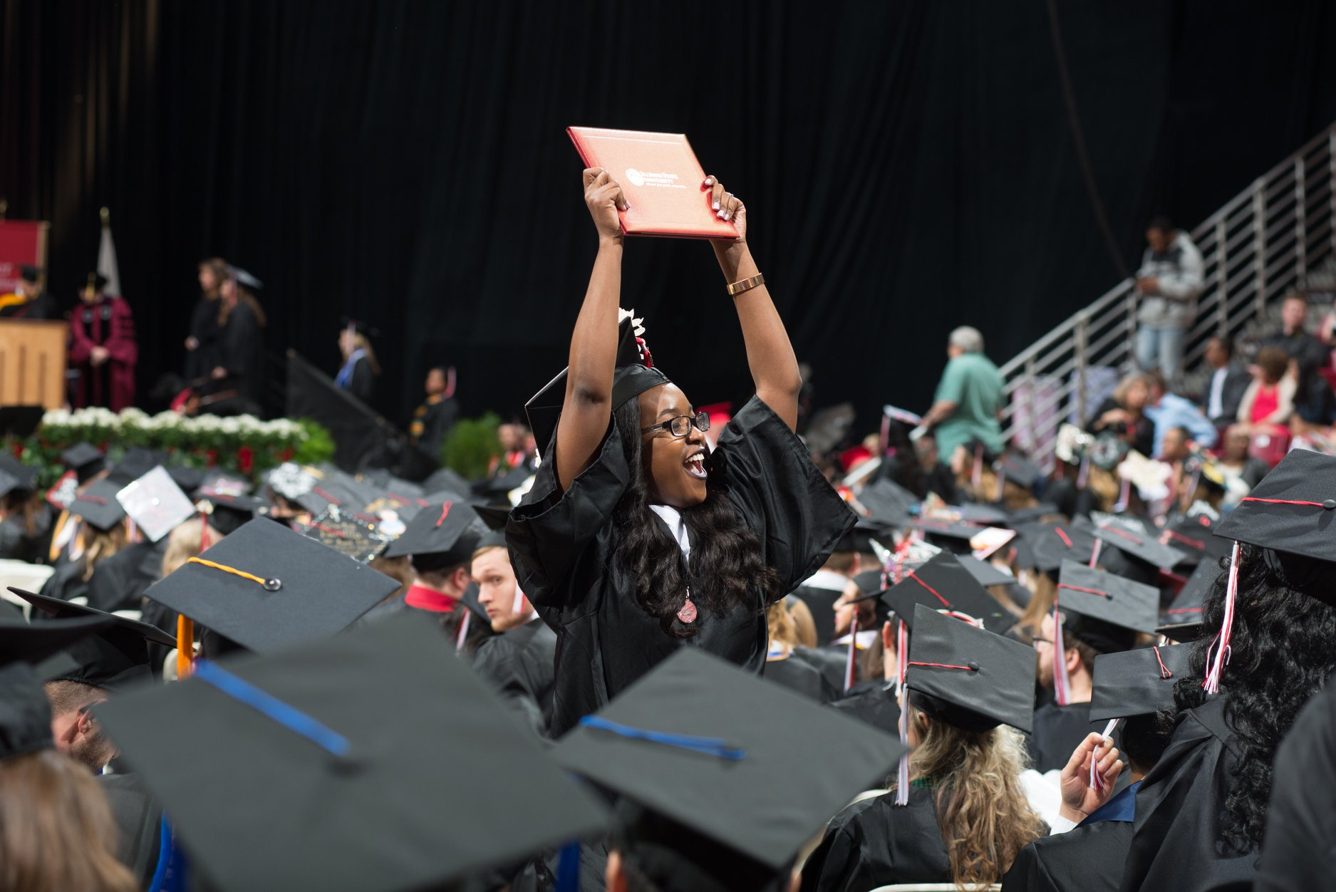 Student celebrates with diploma.