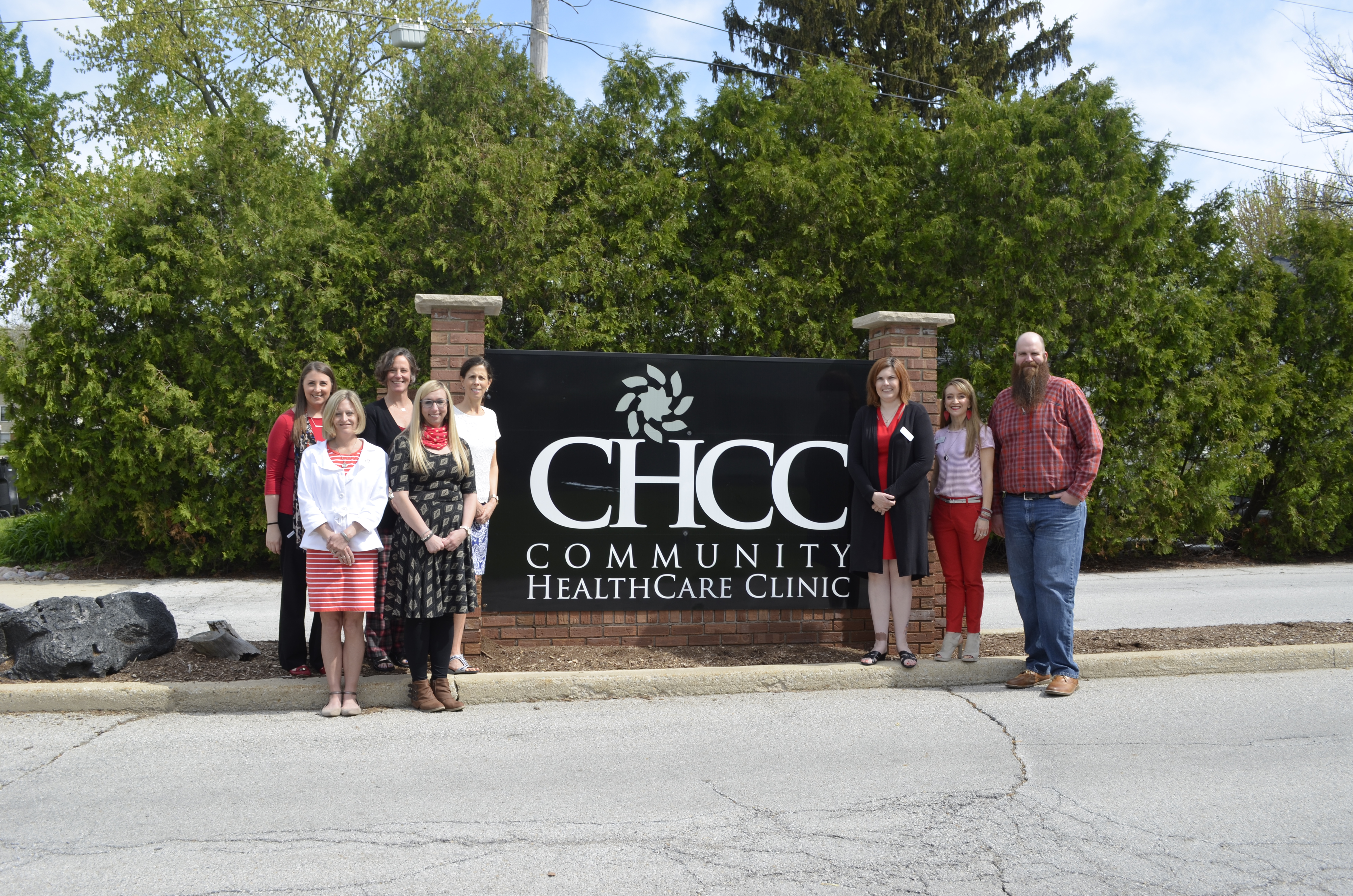 People standing next to CHCC sign