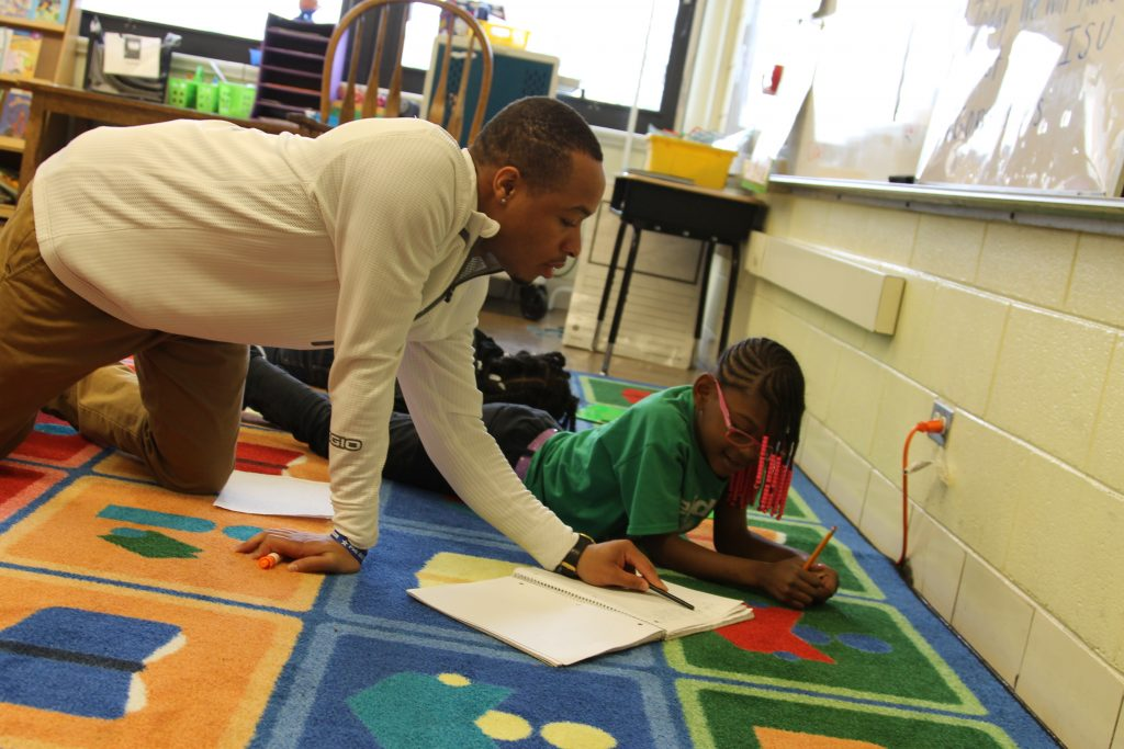 Alum Daniel Jackson works with a student on a literacy lesson.