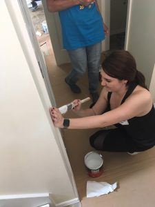 Alumna Emily Vermeire paints in a hallway of the Habitat for Humanity home where Illinois State alumni volunteered their time June 22 as part of #RedbirdImpact Alumni Weekend.