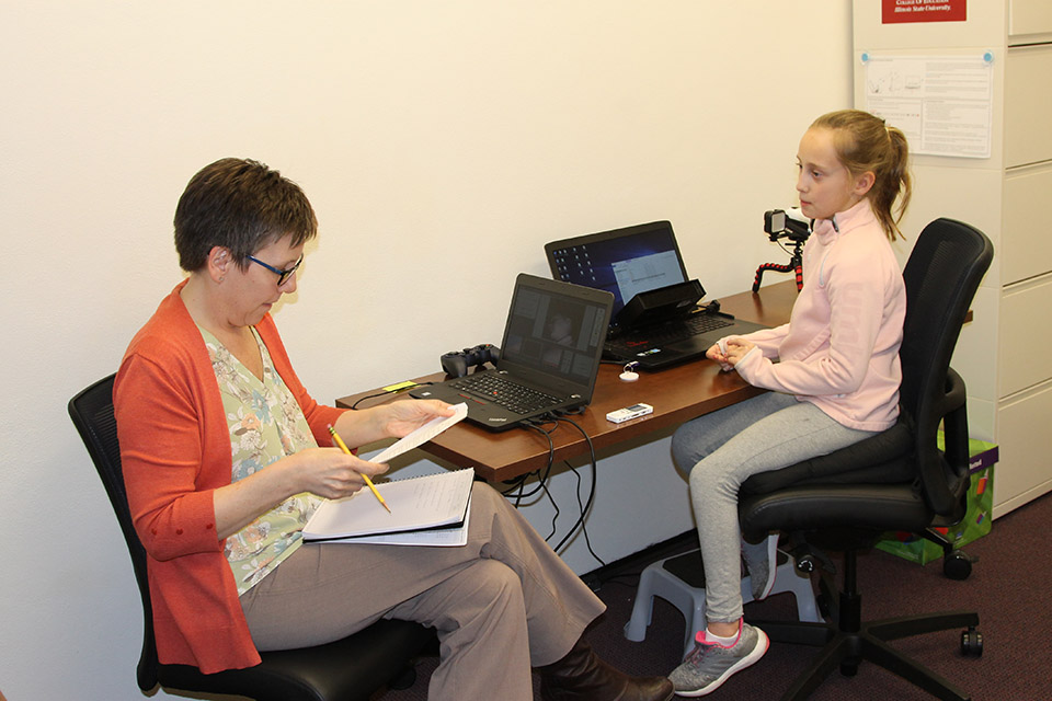 Associate Professor Deborah MacPhee works with a young learner in the EMMA lab.