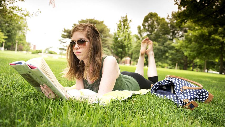 Student reading on Quad