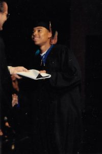 man in graduation attire grabbing diploma