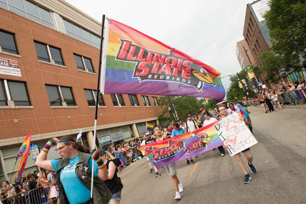Illinois State alumni Dana Niswonger '19 leads the Illinois State University group at the Chicago Pride Parade.