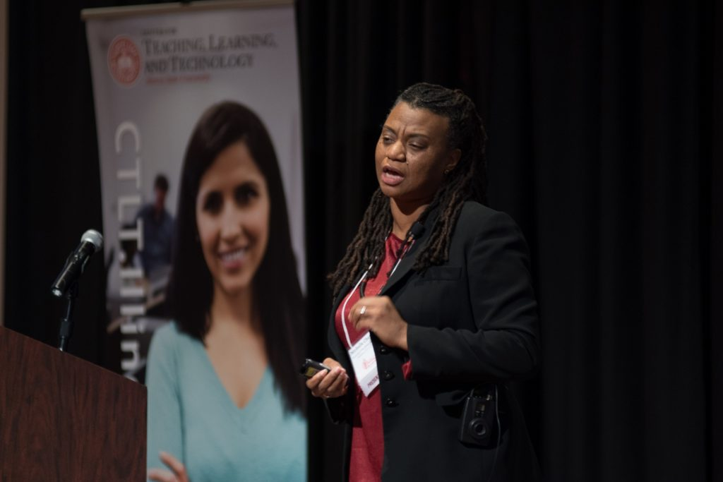 Female professor giving keynote address on stage at luncheon