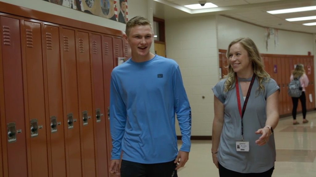 Kateri Gullifor walks through the halls with one of her high school students.