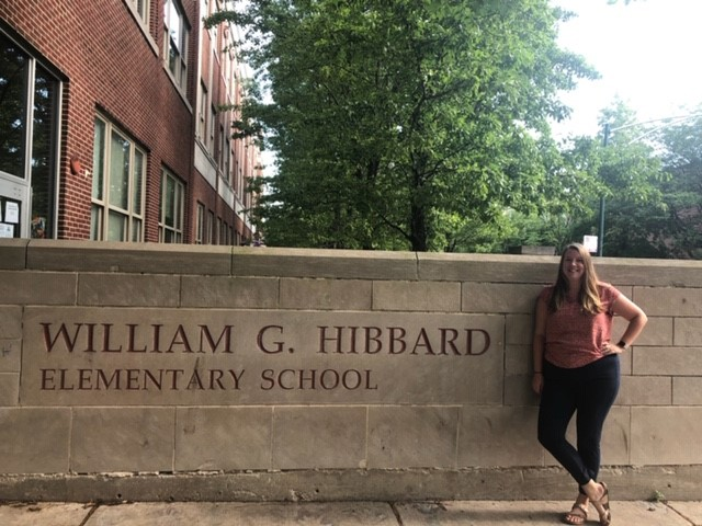 woman standing next to a sign that reads William G. Hibbard Elementary School