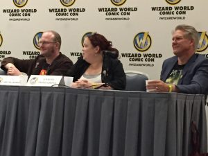 three people seated at a table with the Wizard World logo in the background