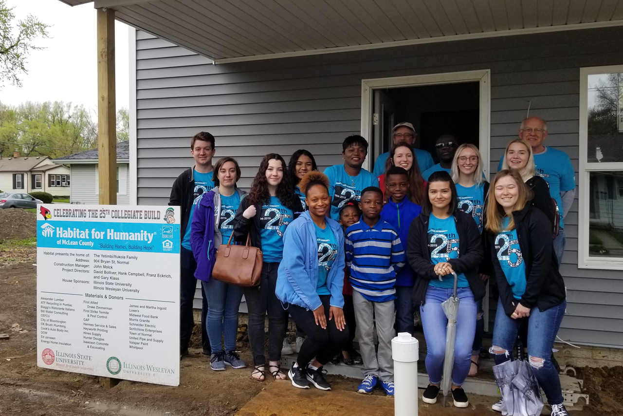 Students pose with a Habitat for Humanity family near the end of their 2018-2019 home build.
