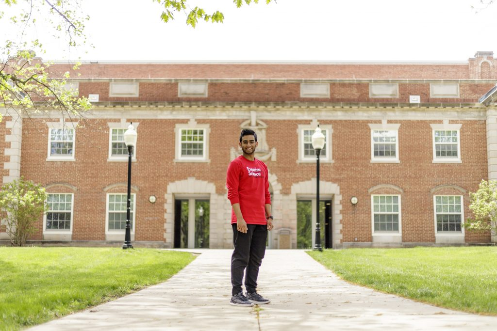Presidential Scholar and Exercise Science major Mohammed Zaman in front of the Student Fitness Center and McCormick Hall.