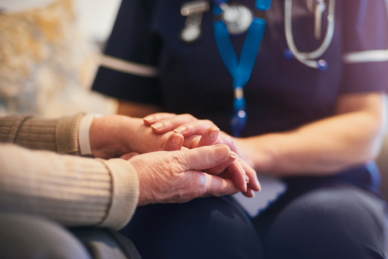 A female nurse consoles a senior patient at home