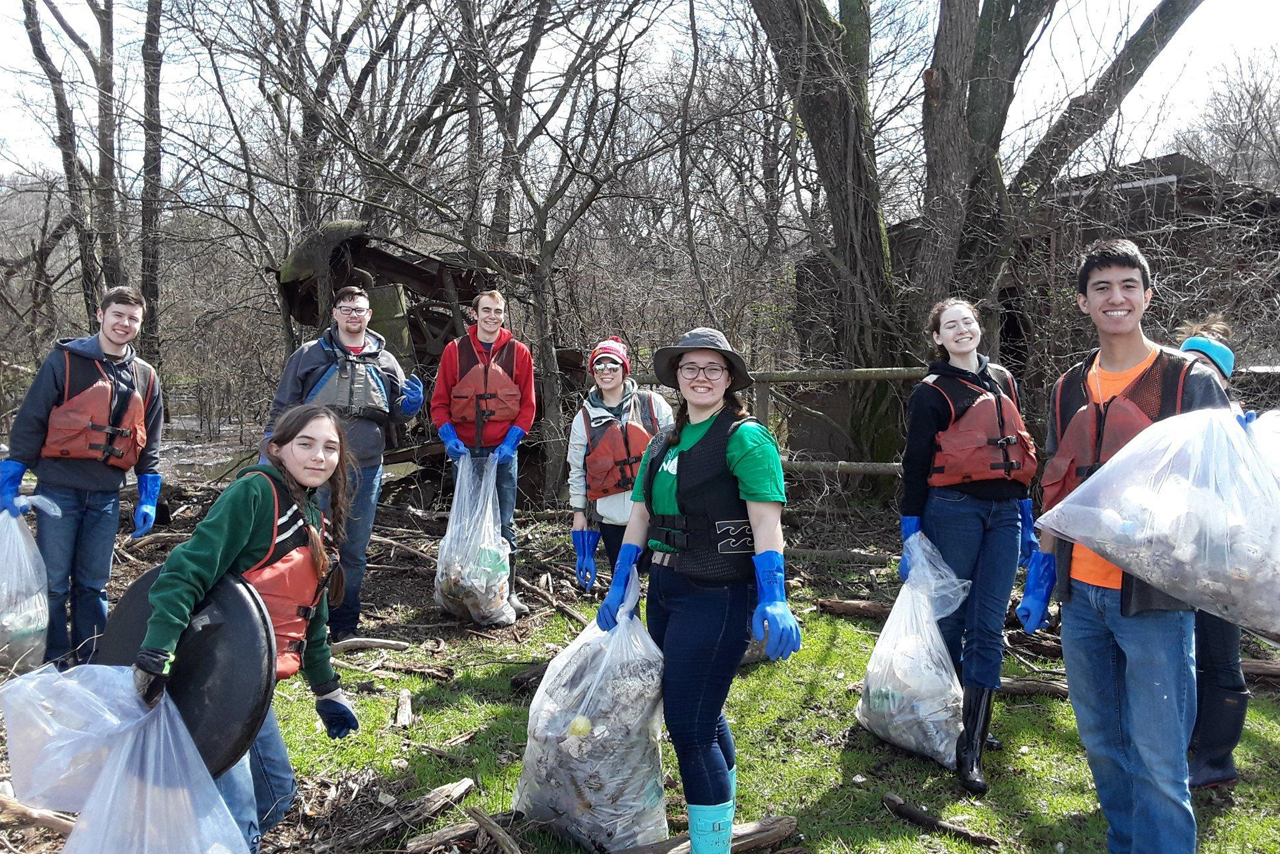 Students collecting bags of trash