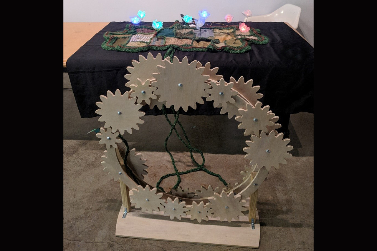 Image of the art piece Windstorm depicting wooden gears, topographic tapestry, and LED flowers.