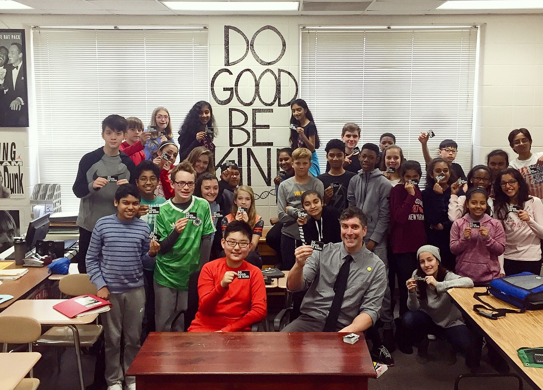 Health sciences alum Scott Todnem wins 2019 National Teacher of the Year award and his students pose with the words Do Good and Be Kind on a sign