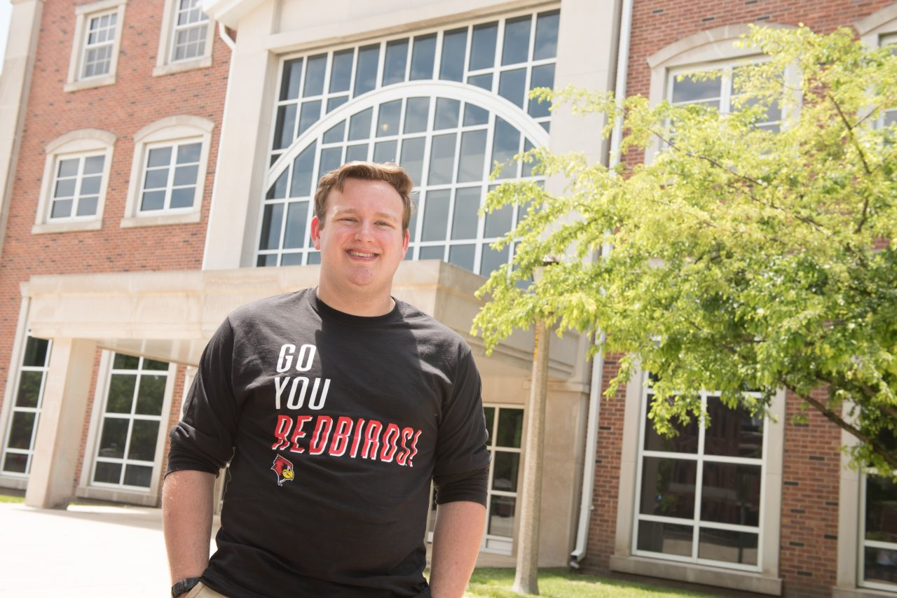 Luke Knecht on campus in front of building