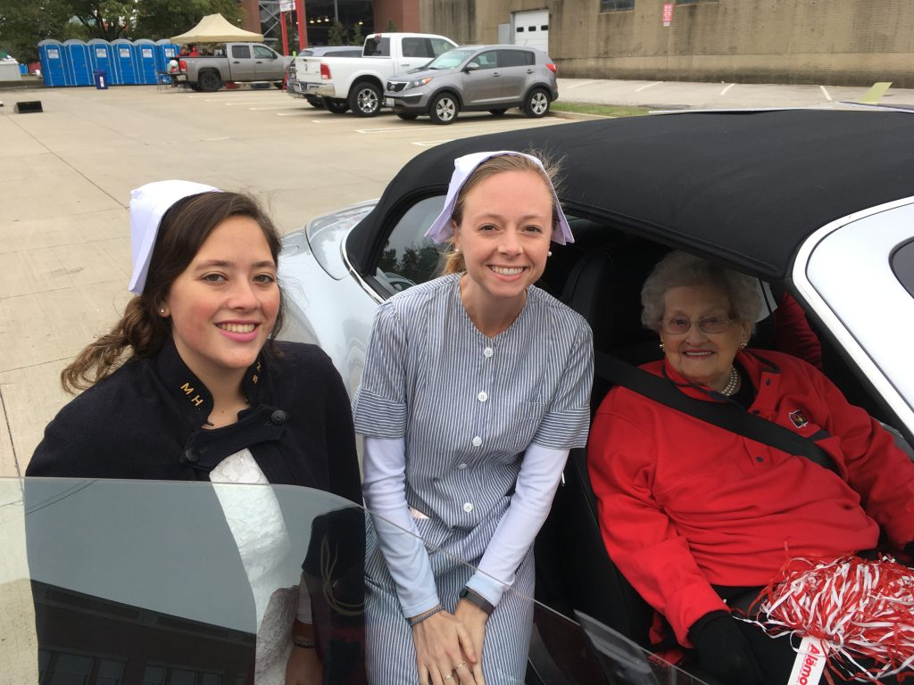 Eleanor Eft with students modeling her uniforms in the 2018 homecoming parade.
