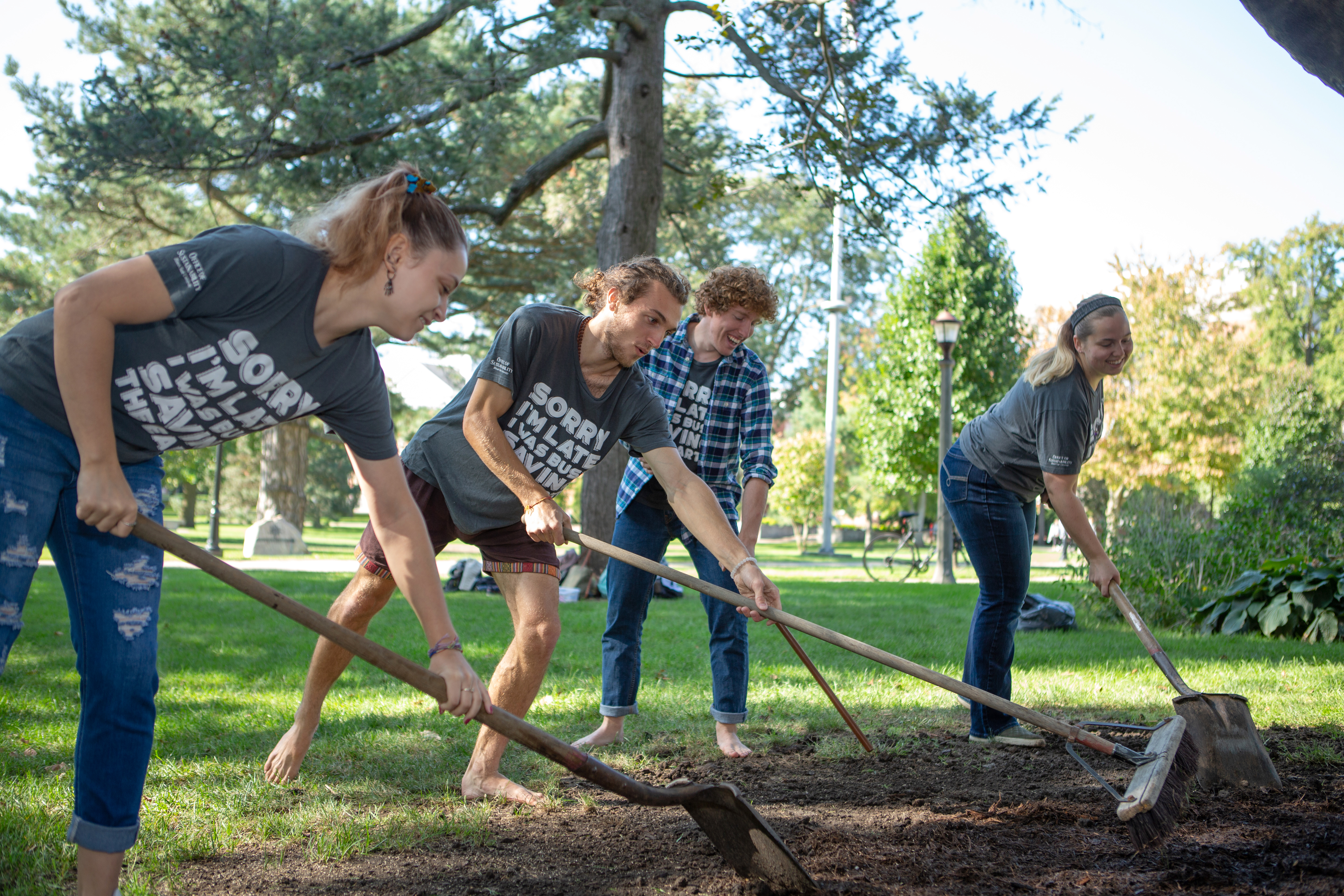 Students raking dirt in the Quad