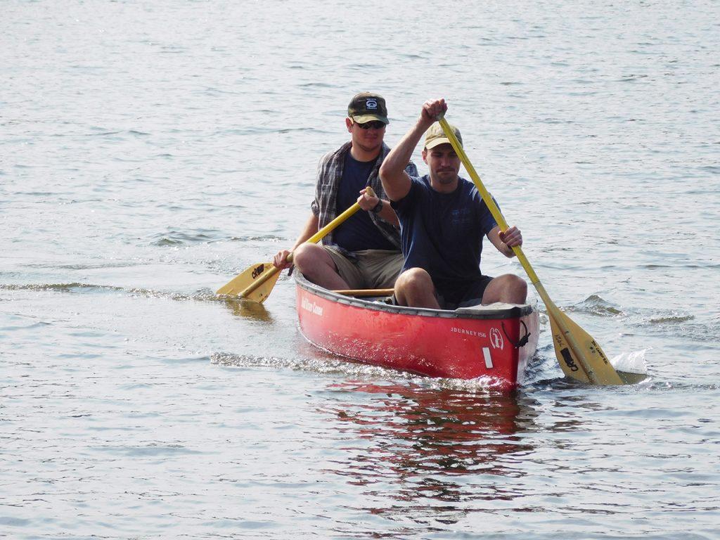 two men rowing in a canoe
