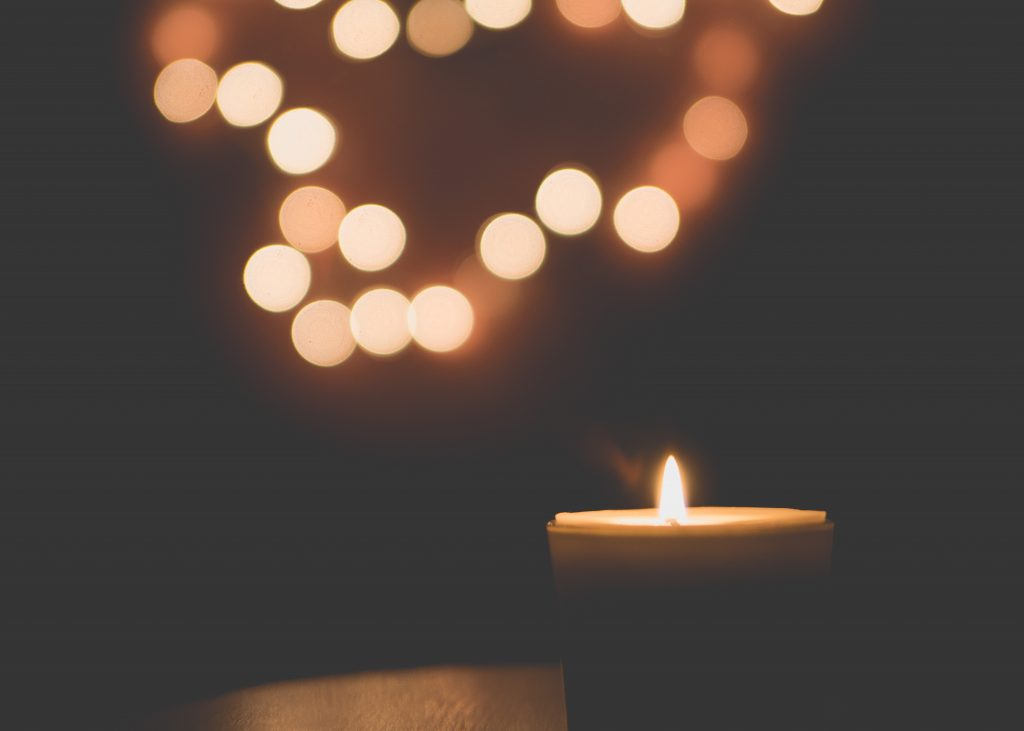 lit candle in darkness
