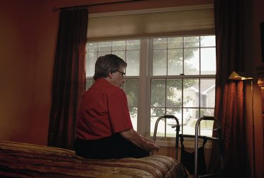Woman alone in a nursing home room