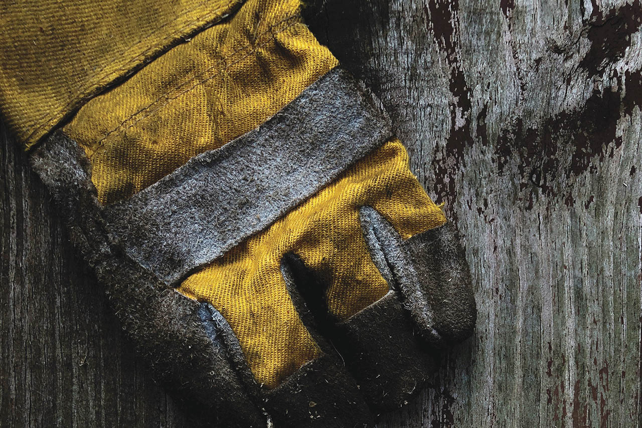 Image from production photo for Sweat/ depicting a yellow work glove on top of a wooden table.