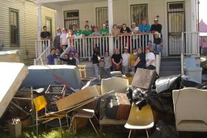 Students post on a porch near a large pile of debris