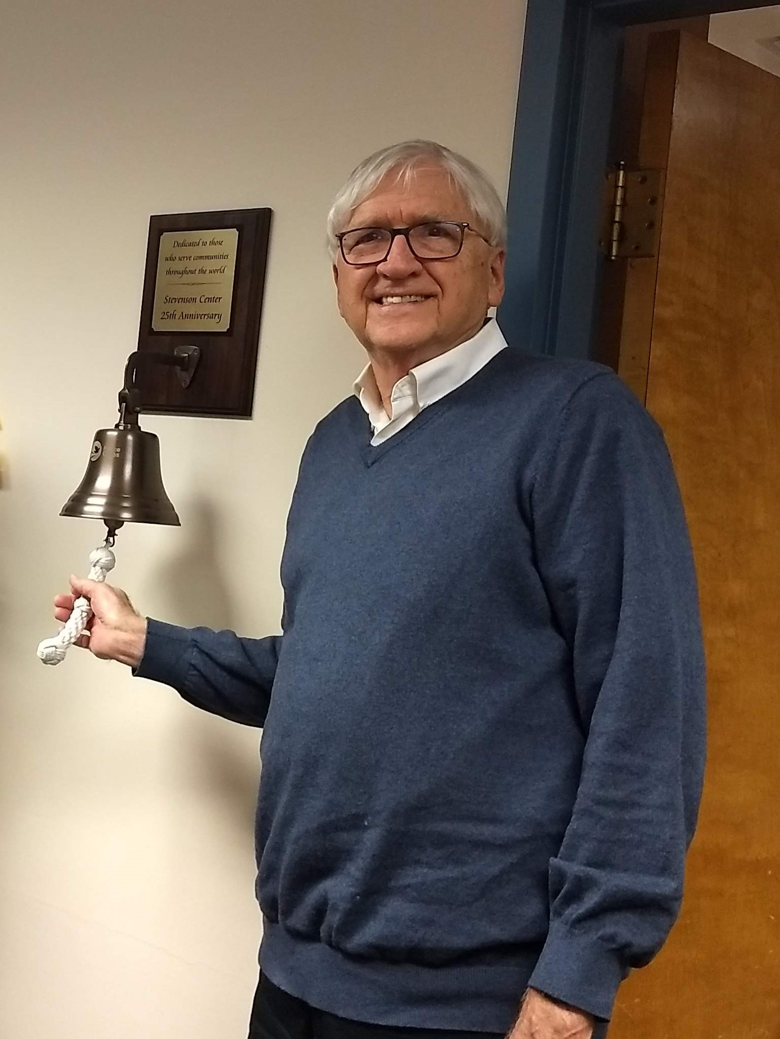 Robert W. Hunt, professor emeritus and founder of the Stevenson Center, ringing the 25th anniversary Peace Corps commemorative bell. The Hunt Family Fund enabled Fellows to attend the <em>Housing Matters!</em> conference.