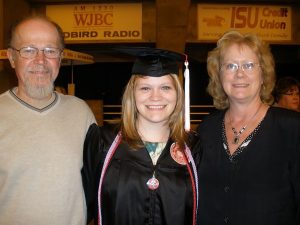 julia o'dell in her graduation cap and gown standing with her parents