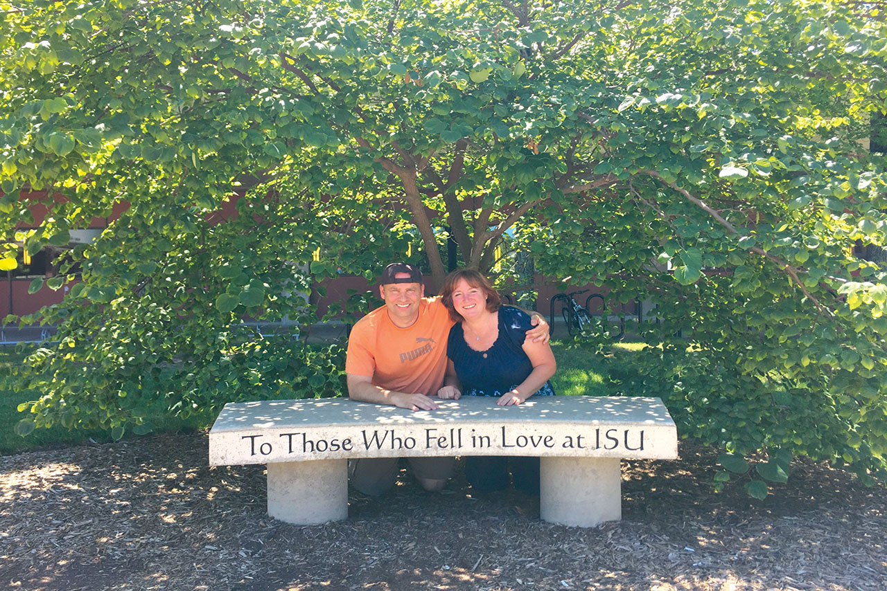 "Couple sitting in front of bench that reads ""To those who fell in love at ISU"""